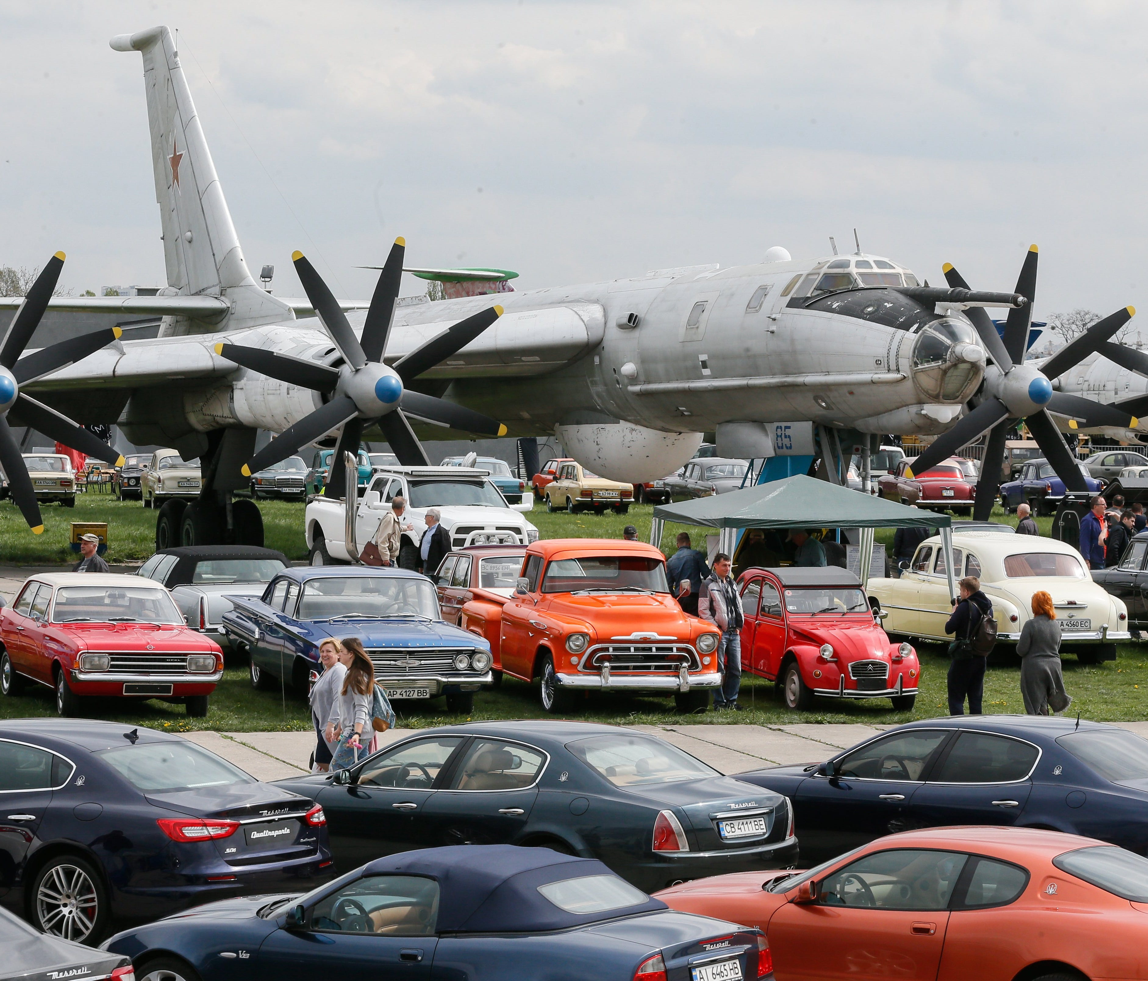 Visitors look at old cars placed in front of a Soviet strategic bomber Tu 95 'Bear.'