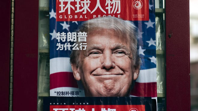 This picture taken on December 14, 2016 shows a advertisement for a magazine featuring US President-elect Donald Trump on the cover at a news stand in Shanghai. China.