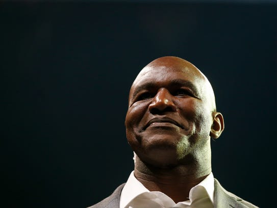 Evander Holyfield smiles to the crowd before the Real