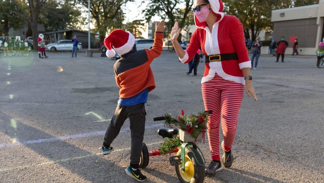 Ashley Lyda, right, and her son Jaxson, left, high five after winning the tricycle race hosted by Breakthrough House.