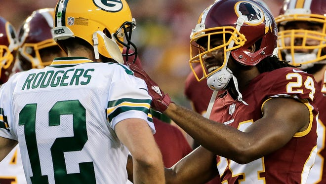 Green Bay Packers quarterback Aaron Rodgers,and Washington cornerback Josh Norman talk during their preseason game Saturday, Aug. 19, 2017, in Landover, Md.
