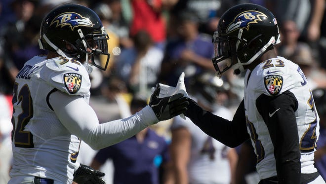 Baltimore Ravens free safety Eric Weddle (32) congratulates strong safety Tony Jefferson for sacking Oakland Raiders quarterback EJ Manuel.