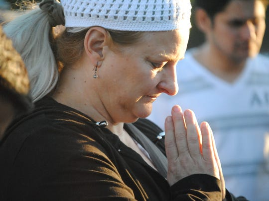 Gray Weisheipl prayed during a moment of silence during a candlelight vigil Wednesday at the University of Nevada, Reno in honor of the victims of Nepal's Saturday, April 25 earthquake that had a magnitude of 7.8 and currently has a rising death toll of more than 5,000.