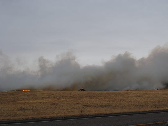 Firefighters battle a fire northwest of Browning Sunday.
