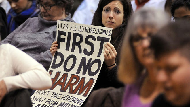 Amy Kuiken, 34, of Dallas, Pa., holds her sign, as she listens to a person's story during a town hall meeting regarding health care at the United Neighborhood Center in Scranton, Pa., Tuesday, Feb. 21, 2017. Sen. Pat Toomey, R-Pa., was invited to speak at the town hall, but did not attend. (Butch Comegys/The Times & Tribune via AP)