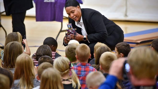 Sawana Kirkland, vice president of the Minnesota Chapter of the National Black Police Association, shows Kennedy Community School students some school supplies and items donated Friday, Sept. 8, in memory of a family who lost a son this summer.