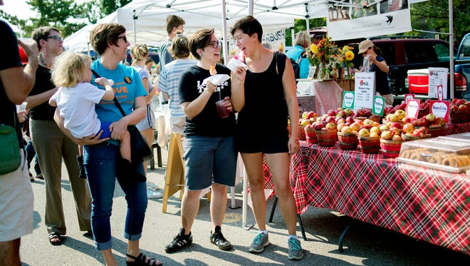 Morgan Doherty, left, and Amanda Niven, right, stand in front of the Country Mill Farms' booth in support of the LGBTQ community on Sunday, Sept. 17, 2017, at the East Lansing Farmer's Market. Country Mill Farms returned to the farmers market two days after a federal judge granted an injunction against the city and its decision to ban farm owner Steve Tennes over his decision not to hold same-sex weddings at this Charlotte farm.