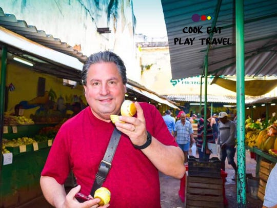 George Meyers holds an orange in a market in Cuba.