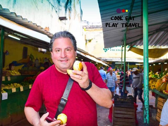 George Meyers holds an orange in a market in Cuba. He and wife Linda have all-inclusive cooking schools and tours in Italy, Mexico and Cuba. Follow them at cookeatplaytravel.com.