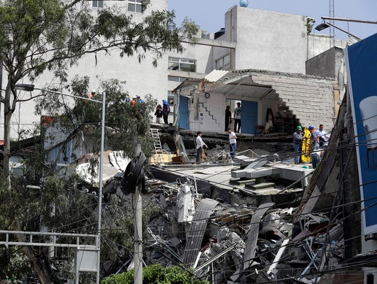 Rescue workers and volunteers search a building that
