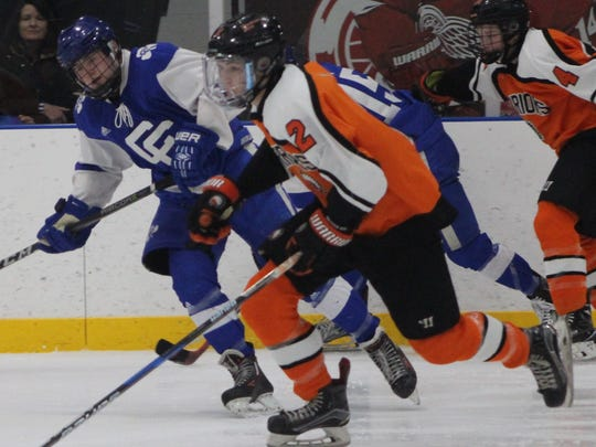 Brother Rice's junior defender Ethan Nystrom (2) races up the ice ahead of a pair of Catholic Central players.