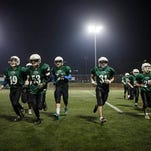 In this photo taken Thursday, Dec. 10, 2015, high school football team Kfar Saba Hawks players warm up for a game against Mazkeret Batya Gorillas in Kfar Saba, Israel. A growing number of native-born Israelis have taken to the army-like strategy, camaraderie and collisions of the gridiron and turned America's Game, once a niche expat activity, into a popular fixture in the Holy Land. (AP Photo/Dan Balilty)