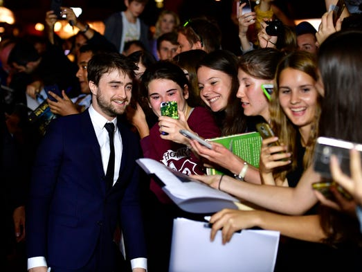 Daniel Radcliffe writes autographs and takes selfies