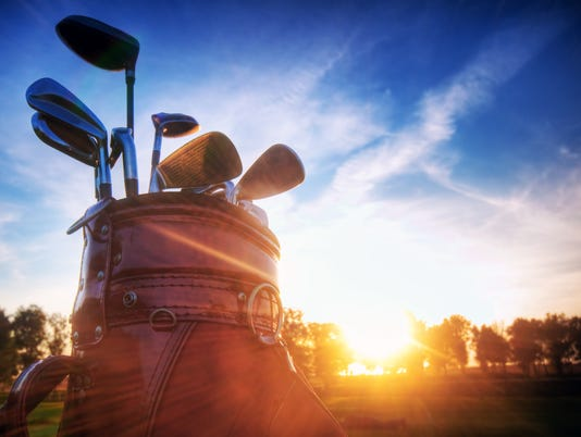Golf gear, clubs at sunset