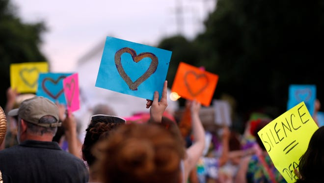 "Participants hold up signs with hearts in honor of victims of the Orlando Pulse nightclub massacre, in the ""New Orleans Pride"" parade, a gay pride parade, in New Orleans on June 18, 2016."