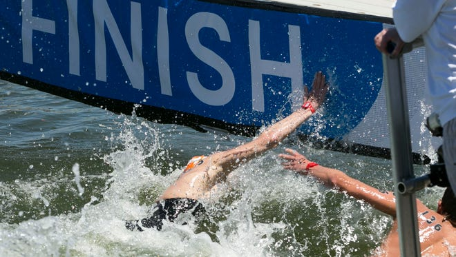 David Heron (left) slaps the finish board before James Brinegar, earning Heron second place during the men's 10 kilometer open water race of the USA Swimming Open Water Nationals at Tempe Town Lake on Friday, May 4, 2018. Heron would get second.