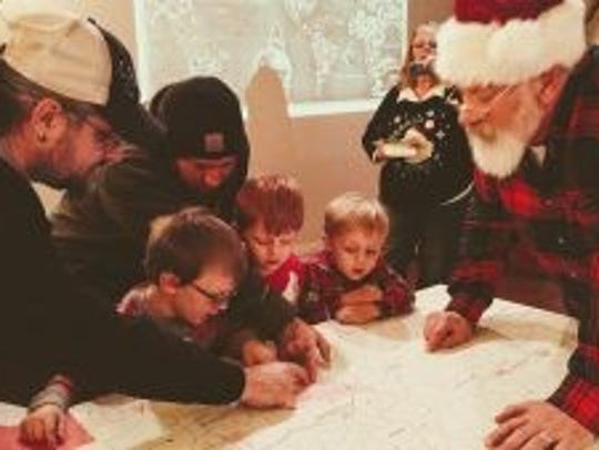 Families help Santa Claus find their homes on a map