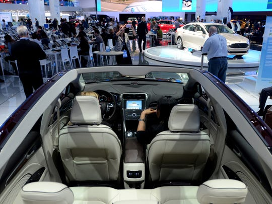A pair of event goers sit inside a Ford Tuesday, Jan. 12, during the North American International Auto Show at Cobo Hall.