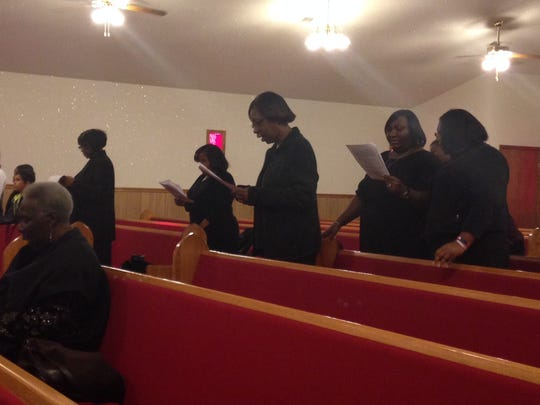 The New Greater Bethel CME Church members, all dressed in black, worship with responsive reading Sunday morning.