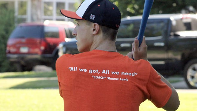 """Logan Zarvell bats for Team Iowa on Friday at McKinley Park in Kewanee. Both teams wore uniform shirts with a slogan from Shaune Lewis, the Kewanee boys basketball coach who died July 2. It reads: """"All we got, All we need."""""""