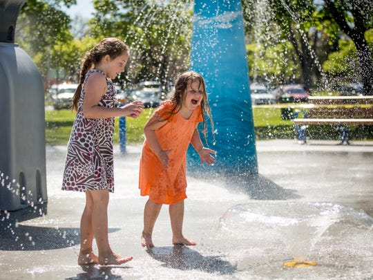Sisters Sara Stoner, 7, and Cheyenne Stoner, 6, scream in excitement as they walk through the splash pad last year at Lakeside Park. The city has turned on the splash pad in preparation for Memorial Day.