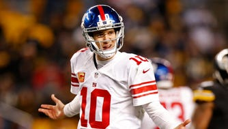 New York Giants quarterback Eli Manning (10) questions a non-call by the referee during Sunday's game.