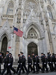 Firefighters walk outside St. Patrick's Cathedral as
