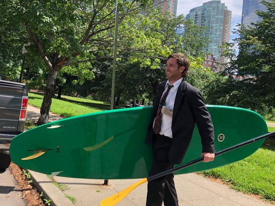 Scott Holt of Jersey City carries his board toward the water June 21, 2018.