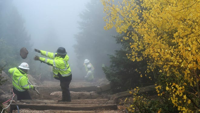In this Oct. 4, 2017, photo, a worker tosses a rock from the work being done at the top of the Manitou Incline on Pikes Peak during a fog day in Manitou Springs, Colo. Ties are being replaced and the popular exercise destination is being made safer. (Jerilee Bennett/The Gazette via AP)