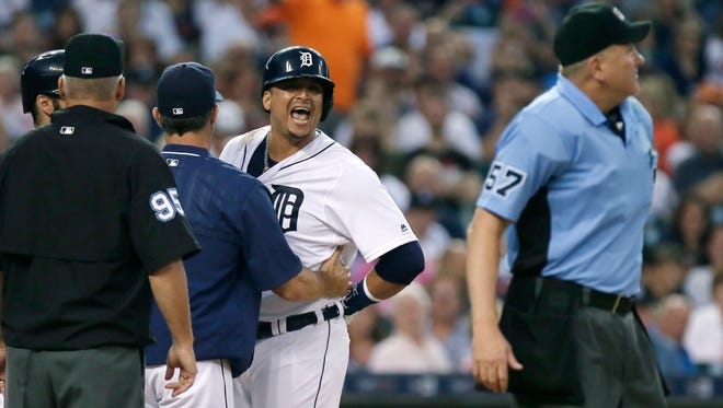 Detroit Tigers' Victor Martinez continues to yell at home plate umpire Mike Everitt (57) as he is escorted off the field by manager Brad Ausmus following his ejection during the third inning of a baseball game against the Los Angeles Angels on Saturday, Aug. 27, 2016, in Detroit. (AP Photo/Duane Burleson)