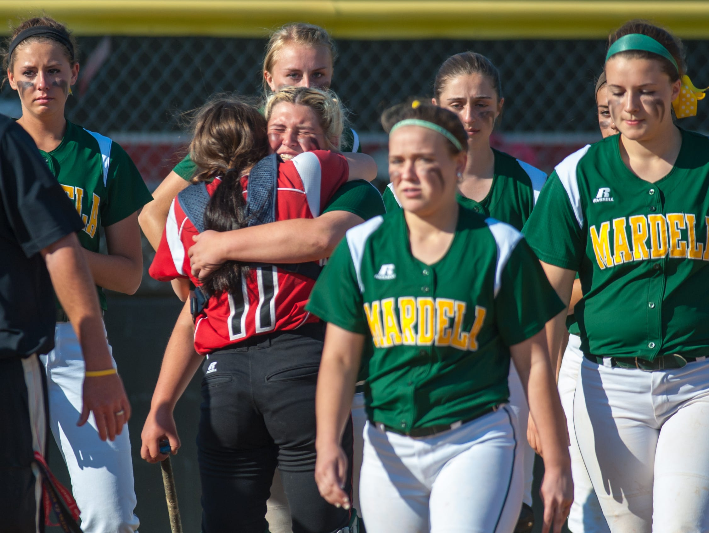 Mardela third baseman Kasey Goshorn (15) and Colonel RIchardson catcher Emily Cox (11) share a hug following the Warriors 2-1 loss in the MPSSAA 1A East Softball Region Finals on Friday afternoon in Federalsburg.