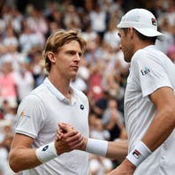 Kevin Anderson of South Africa (L) at the net with John Isner of the US whom he defeated in their semi final match during the Wimbledon Championships at the All England Lawn Tennis Club, in London, Britain, 13 July 2018.