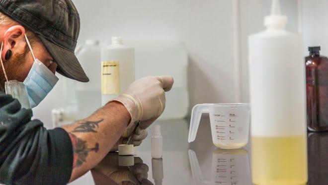 Manager Monte Van Buskirk measures ingredients used to make vapor liquid inside a lab at GoVapors in Cedar City, Feb. 10, 2016.