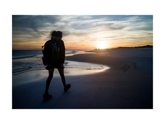 """Gretchen Matt hikes into the sunset along Pensacola Beach as she nears the end of her trip on Thursday, March 2, 2017. """"It felt like a strangely beautiful ending to such a challenging trip,"""" said Matt."""