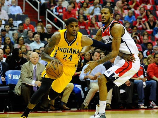 May 11, 2014; Washington, DC, USA; Indiana Pacers small forward Paul George (24) dribbles the ball as Washington Wizards small forward Trevor Ariza (1) defends during the first half in game four of the second round of the 2014 NBA Playoffs at Verizon Center. Mandatory Credit: Brad Mills-USA TODAY Sports