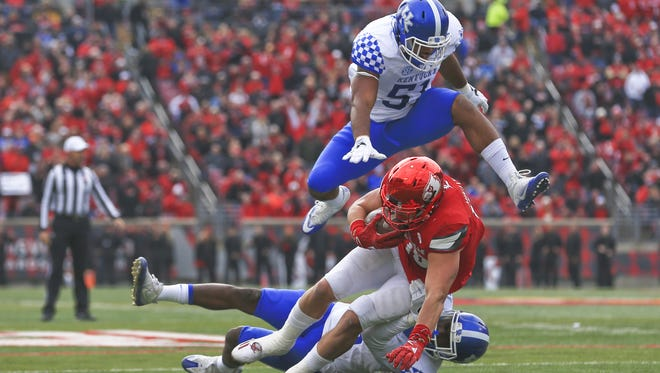 Kentucky's Marcus McWilson stops Louisville's Cole Hikutini as Courtney Love hurdles over in the 2016 Governor's Cup.