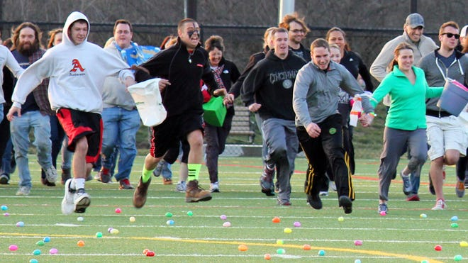 Adults of all ages make a mad dash across the field to collect Easter eggs and possibly nab big prizes during the 2013 partner egg hunt at Riverside Park.