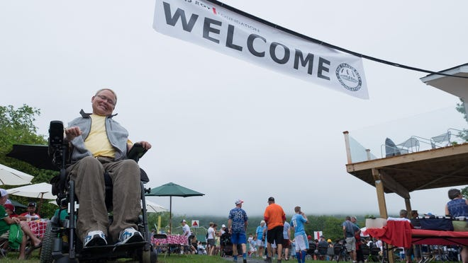 Travis Roy poses under the welcome sign at Little Fenway for the 15th annual Travis Roy Wiffle Ball Tournament in 2016.