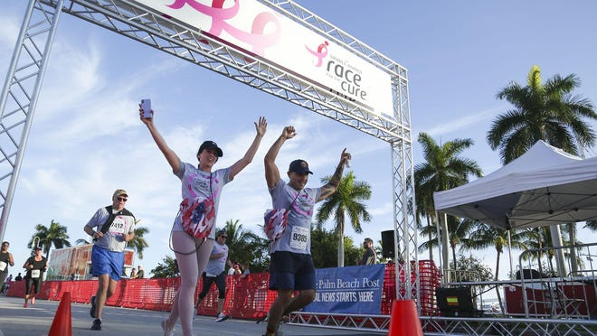 Runners cross the finish line during the 5K event at the Susan G. Komen Race for the Cure on South Flagler Drive in downtown West Palm Beach in January 2020. The coronavirus pandemic has canceled the run for this year.