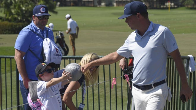 Champion Keith Mitchell bumps fists with 5-year-old Benjamin Titkemeier during the third round of the 2019 Honda Classic at PGA National in Palm Beach Gardens.