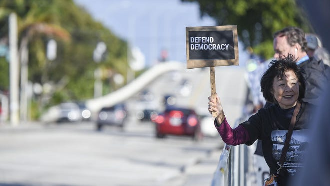 A protester holds up a sign on Southern Boulevard along President Trump's motorcade route on Sunday, Jan. 5, 2020, in West Palm Beach.
