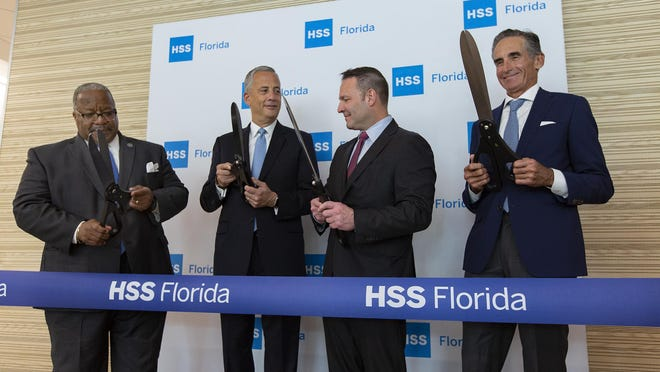 (L to R) West Palm Beach Mayor Keith James prepares to help cut the ribbon with Louis A. Shapiro, president and CEO of HSS, Bryan Kelly, MD, HSS surgeon-in-chief and David Altchek, MD, founding medical director of HSS Florida at the grand opening of HSS Florida in West Palm Beach, Feb. 10, 2020. HSS Florida opened a new 60,000 square foot center that will bring top doctors to Florida patients dealing with orthopedic health issues. The center will open with a staff of between 30 and 50, including radiologists, technicians and physical therapists.