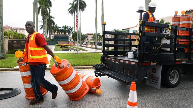 Frank Moise of Bob's Barricades unloads traffic cones to make room for construction in Palm Beach.