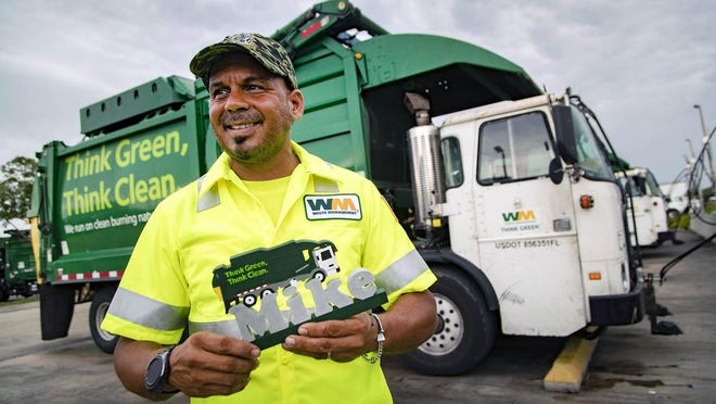 Mike Hernandez, a driver for Waste Management, holds a carving made by a customer on his Wellington route, May 21, 2020.