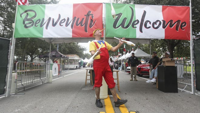Miami-based juggler Tim Irwin juggles in front of the 17th annual Feast of Little Italy in Jupiter in November 2019. Despite a rainy afternoon, hundreds visited the festival, which featured Italian food, carnival rides and performances by artists.