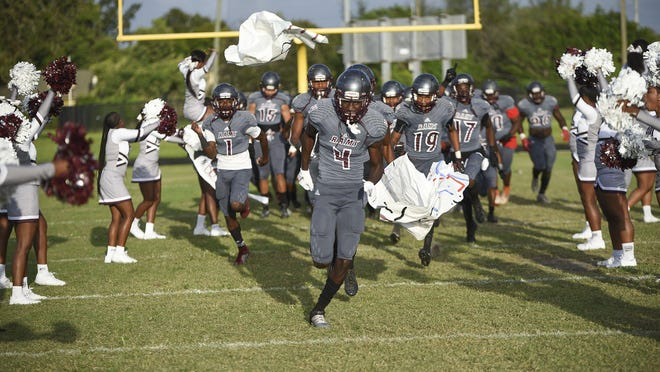 The Palm Beach Lakes football takes the field before a game last season against Pahokee. The start of the fall sports season has been delayed statewide until at least Aug. 24