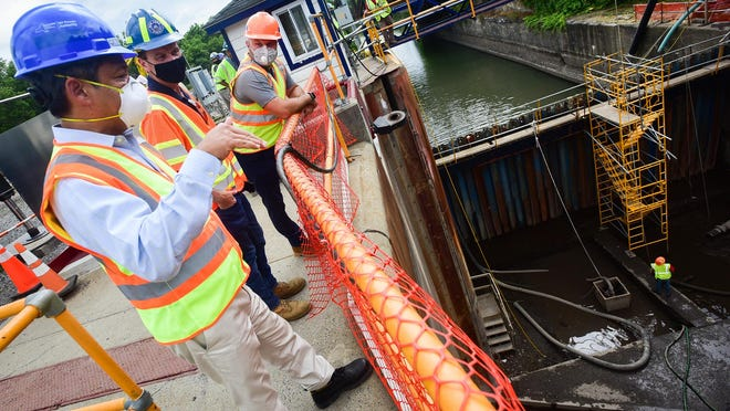 Gil Quiniones, President/ CEO of New York Power Authority, talks to others about a temporary coffer dam that is now in place at Lock 19 in Schuyler on Wednesday, July 1, 2020. The dam is temporarily holding water as work continues inside the lock.