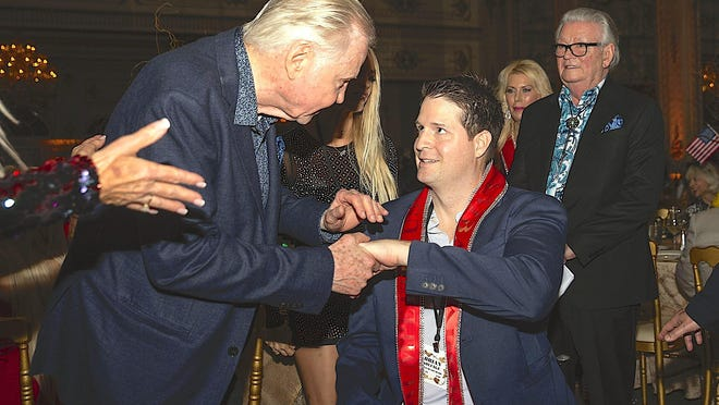 Actor John Voight, left, greets Brian Kolfage, founder of a viral online campaign to raise funds for President Donald Trump's border wall, at last year's Trumpettes USA Gala at the Mar-a-Lago Club.