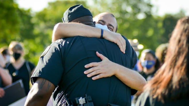 "Jim McDonald, Pflugerville City Council, hugs police Lt. Makeba Lewis before the ""In Remembrance"" march on Saturday during a Black Lives Matter protest. The City Council took steps Tuesday to create a city Equity Commission."