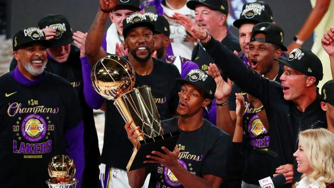 Rajon Rondo holds the trophy as the Lakers celebrate their 2020 NBA championship.